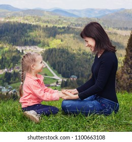 Mom and little daughter are sitting on top of the mountain. Square. The concept of family, yoga, travel.