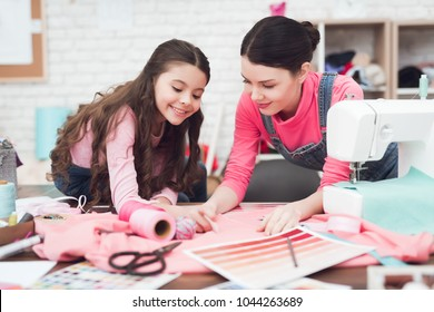 Mom and little daughter together sew clothes. They are in the sewing workshop. They are in a good mood.