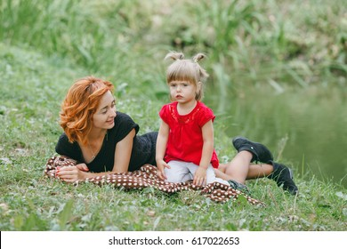 mom and little daughter walking in green summer park