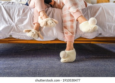 mom and little girl sitting on bed wearing slippers. Cozy homeware mom and daughter.