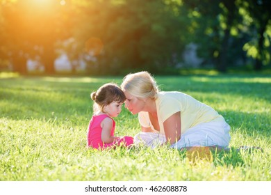 Mom and little girl softly whispering face to face in the sunset park.Lens flare