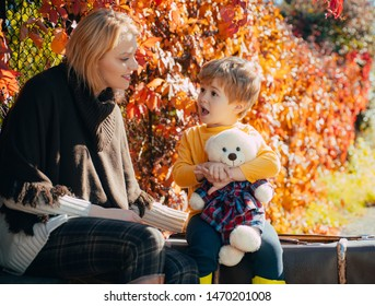 Mom little son communicate autumn foliage background. Trustful relations. Parenthood and upbringing. Love and trust. Cute boy talking with mom. Family conversation. Tell mom his secret. Mothers day.