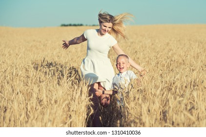 Mom and little son are running around the wheat field.