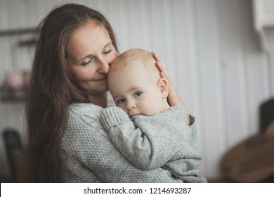 Mom with long hair hugging baby boy playing with son in the kitchen in real interior. Concept of gentle happy motherhood