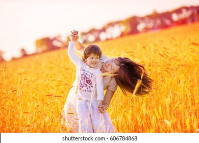 Mom with long hair and son dancing in the middle of a ripe wheat field