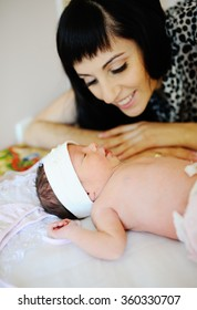Mom looks at newborn daughter