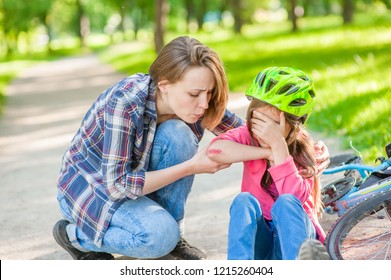 Mom looks at the wound of his daughter, who fell from a bicycle