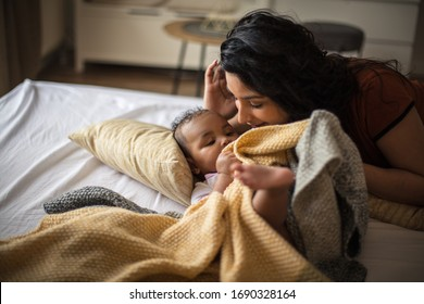 Mom loves you with all her heart and soul. African American mother with her daughter on bed.a