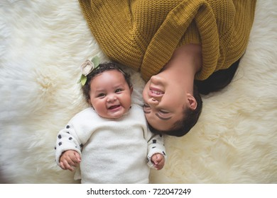 Mom lying down with baby girl on white fuzzy rug
