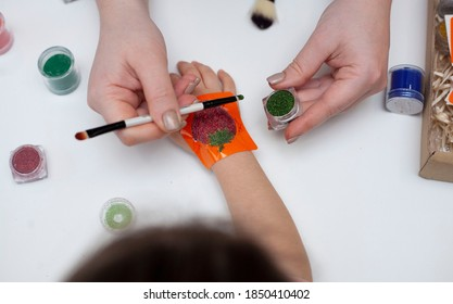 Mom makes a tattoo for her daughter. Women's hands makes a tattoo on a child's hand. Body art