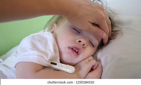mom measures temperature with thermometer to baby and caresses child with hand. close-up. baby sleeps in hospital ward on white bed.