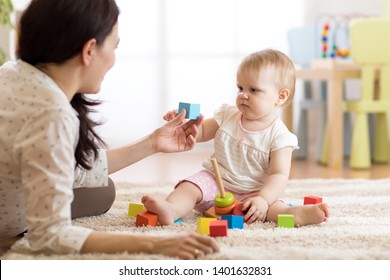 Mom or nanny playing with little child, indoors