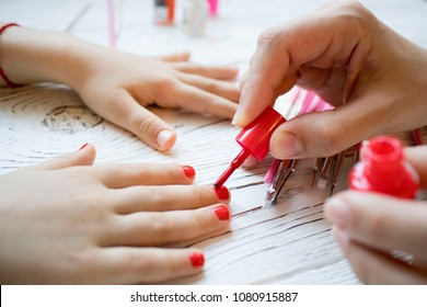 mom paints daughter's nails on hands with red nail Polish on white table, beautiful nails concept, manicure