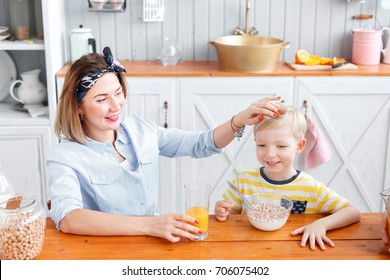 Mom pats the boy on the head. son and young mother in the kitchen eating Breakfast.