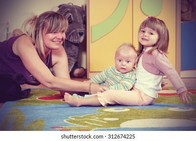 Mom playing with children in nursery