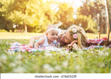 Mom playing with her baby girl while having a picnic in the park.