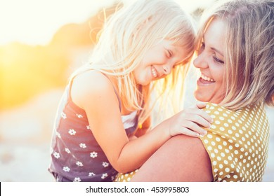 Mom playing with her child outdoors in sunlight