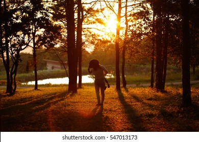 Mom playing with her child outdoors in sunlight,Beautiful green pine trees on Carpathian mountains in Ukraine,Mother and son playing on the beach at the sunset time. Concept of friendly family.