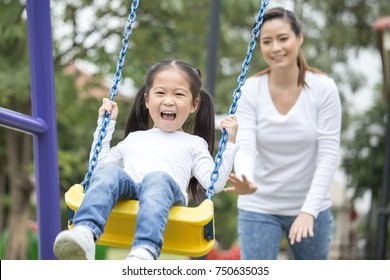 Mom is playing with her little daughter on a terrace with swings. Family lifestyle Concept. Beautiful family is having fun outside.