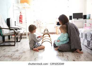 Mom plays with children on the floor with a Waldorf rainbow wooden toy arched building blocks, a real light interior