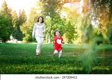 Mom plays with her daughter in the summer park
