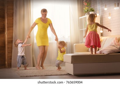 Mom plays with two children in the room. A woman is playing with twins of two years