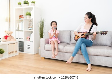 Mom plays the wooden guitar daughter sing the songs. They have a warm family time over the weekend.