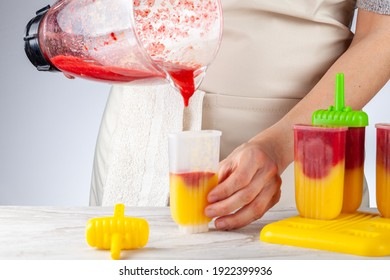 A mom is preparing homemade all natural fruit popsicles. She is filling bpa free plastic molds with layers of pureed mango and berry medley before freezing them. She pours puree from glass mixer bowl.