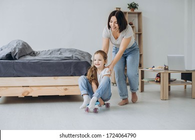 Mom with preschool daughter playing with skate in living room.