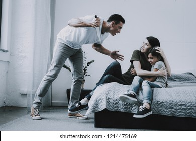 Mom Protects Girl From Threating Dad with Knife. Father Screams at Woman Who Hugs Scared Daughter Lying on Gray Bed Cries in Fear in Bright Bedroom. Quarrel and Family Violence Concept