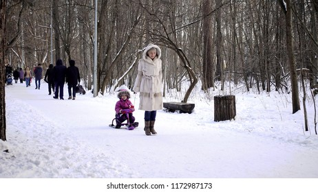 Mom pulls a sled with a child. They walk in the winter forest. Daughter in a warm winter overall. A woman of European appearance in a white mink coat.
