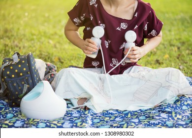 Mom pumping milk to bottles by Automatic breast pump machine in park with foliage sunset bokeh background. breastmilk is the best healthy nutrition food for newborn baby.