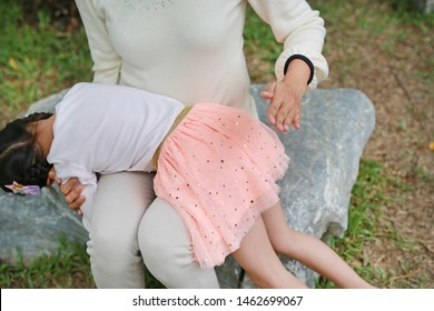 Mom punishing daughter by hitting with her hand. Mother hit her children outdoor. Family violence concept.