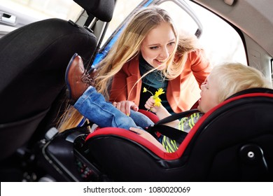 mom puts the child in the car seat and fasten seat belts. Safe transportation of children in the car