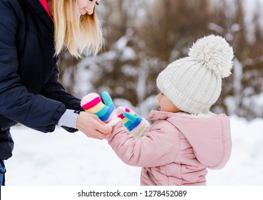 Mom puts on gloves little girl in winter forest