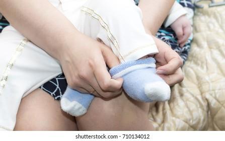Mom puts on socks baby