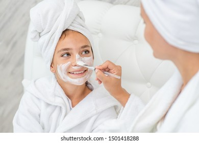 Mom puts white cream on her  smiling daughter's face at home