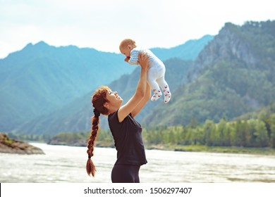 mom raises the child in her arms up