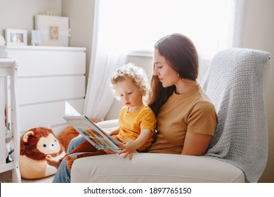Mom reading book with baby boy toddler at home. Early age children education development. Mother and child kid spending time together. Family authentic candid lifestyle.