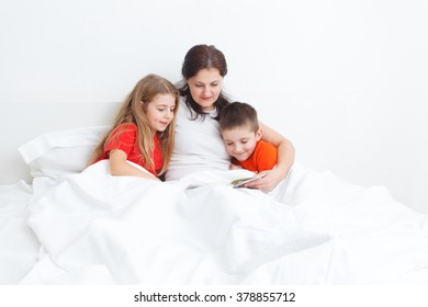mom reading a book in bed for her kids before sleep