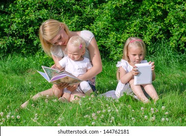 Mom reading book to daughter. Other is playing with computer.