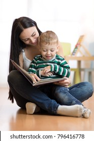 Mom reads with child sitting on floor in nursery
