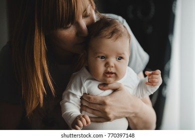 Mom with red hair holds dreamy little baby in her arms