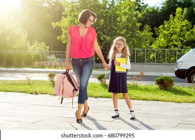 Mom and schoolgirl of primary school holding hands. The parent takes the child to school. Outdoors, return to the concept of the school