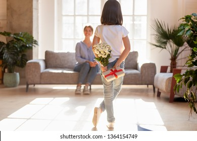 Mom sitting on sofa focus on small daughter rear view hide behind back surprise for mum holding bouquet of flowers prepare gift box. Mothers Day celebration, special occasions family holidays concept