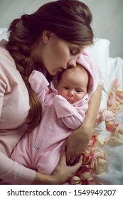 mom with a small newborn daughter lying on the bed in the bedroom
