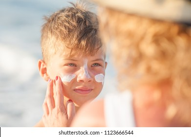 Mom smears his son's face with sunscreen