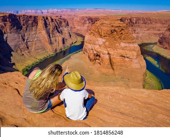 Mom and son admire panorama of Horseshoe Bend, Page Arizona, the Colorado River and mass made of sandstone, has become major tourist destination.