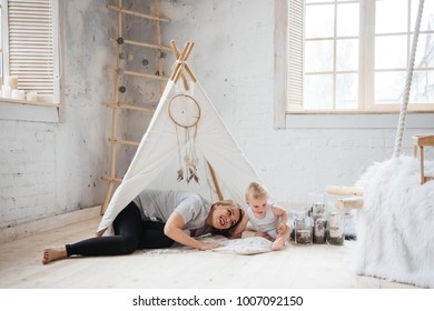 Mom and son with blond hair near the window. A room in Scandinavian style. They embrace, they play in their pajamas. Suspended bed. children's wigwam.