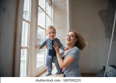 Mom and son with blond hair near the window. A room in Scandinavian style. Near the window. They embrace, they play in their pajamas. Suspended bed.